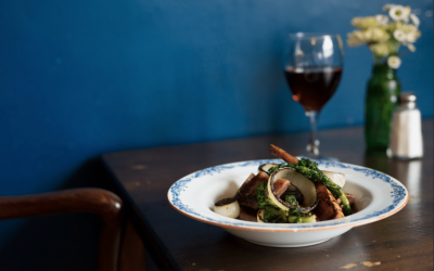 A main dish served on the table with a glass of red wine and a vase of flowers. Photographed against a dark blue wall.