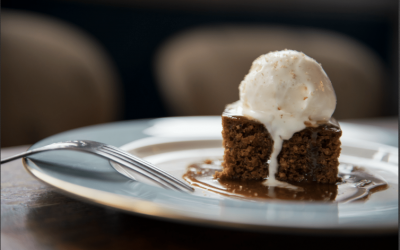 Sticky toffee pudding with ice cream served on a blue plate