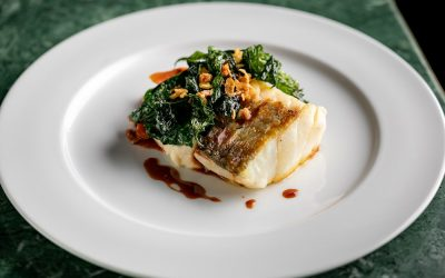 A large white plate with a piece of pan-fried white fish topped with kale and sauce