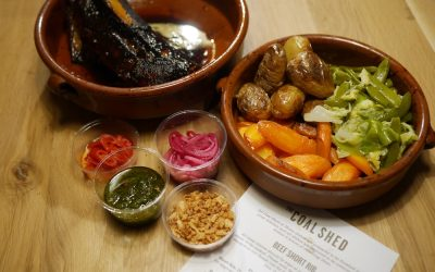 A bowl of sides including potatoes and carrots, a plate of chargrilled meat with dips and sundries. Presented with the Coal Shed paper menu.
