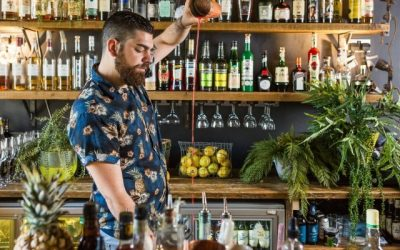 Bartender pouring a cocktail at a height in front of a botanical themes bar.