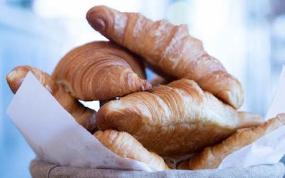Freshly baked croissants piled up in a basket with natural light in the background.
