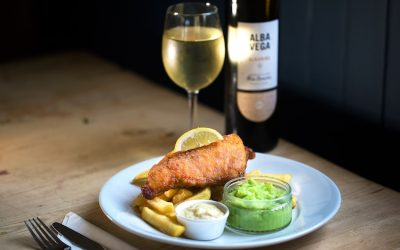 Battered fish with chunky chips and pots of mushy peas and tartare sauce. Served with a bottle of white wine.