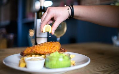 Battered fish and chips with mushy peas and a squeeze of lemon served at a pub.