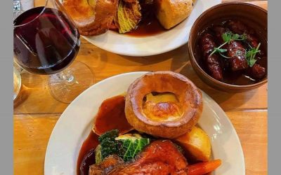Beef roast dinners with Yorkshire puddings, a glass of red wine and gravy. Both served on white dinner plates.