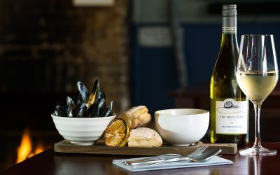 A platter of moules marinière, rustic bread and white wine. Displayed in front of an open fire.