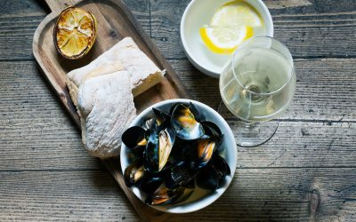 Mussels served in a bowl on a wooden board with fresh bread and grilled lemon. Photographed against a wooden table.
