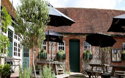Exterior of red-brick pub with trees and black parasols on the tables.