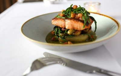 Salmon with samphire and a sauce, served in a shallow ceramic bowl on a white table cloth.