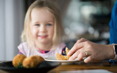Arancini being served on a plate with a happy child