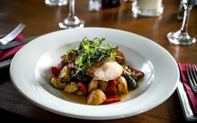 A large shallow white bowl serve with roasted new potatoes and Mediterranean vegetables topped with a piece of cod and garnished with microgreens.