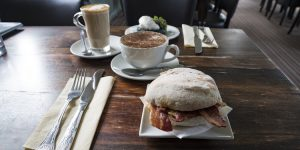 Breakfast roll and coffees served at the table with cutlery