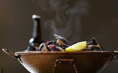 Steaming mussels in a copper dish with a wedge of lemon and a bottle of beer
