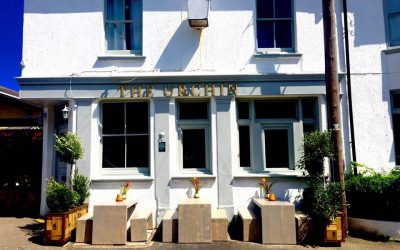 Exterior photography of the white painted pub building with the sun shining, plants and outside seating.