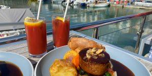 sunday roast on the deck with boats in the background