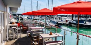 A row of tables with red parasols facing out on the Brighton marina front