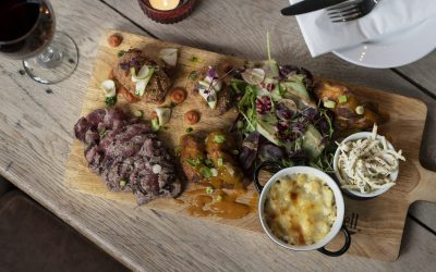 A wooden chopping board serving slice meat, salad, a pot of coleslaw and a pot of sauce with a glass of red wine.