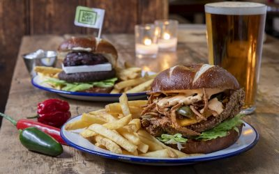 Enamel plates of burgers and fries served on a wooden dining table with tealights and a pint of beer.
