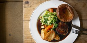 Overhead shot of a Sunday roast with potatoes, greens, carrots and a Yorkshire pudding.