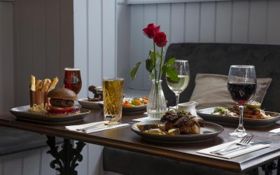 Roast dinners and burgers served at the table with glasses of wine and beer
