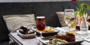 Cushioned indoor seating serving plates of food with a glass of ale