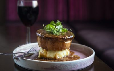 A shortcrust pie sat on a bed of mashed potatoes with gravy and a garnish. Served alongside a glass of wine.