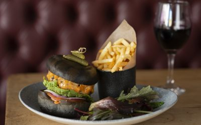 Burger in a black bun with a portion of skinny chips and some salad.