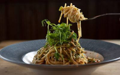 Spaghetti with microgreens served in a blue rimmed bowl and fork