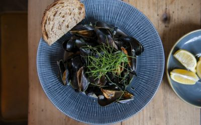 A bowl of mussels in a garlic sauce with crusty bread, fresh herbs and lemon