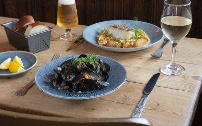 A bowl of moules marinière and a fish dish both served on a wooden table with a glass of wine and beer.