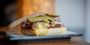 Panini sandwich with melted cheese, red cabbage and pickles. Served on a marble tray.