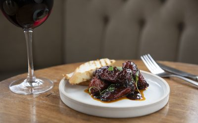 A small plate of sticky ribs served with a glass of red wine.