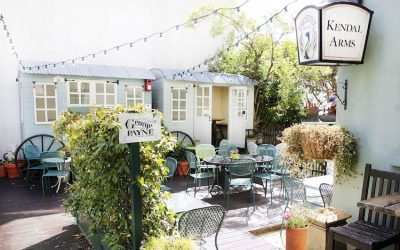 The garden at The George Payne Hove with plants, seating and a vintage caravan