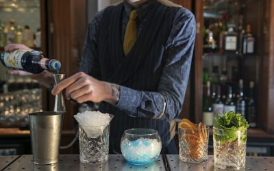 Bartender preparing cocktails with different glasses and garnishes.