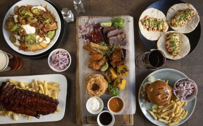 Overhead photograph of a feast of sharing dishes laid out on a wooden table.