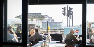 A view of the West pier taken from inside The New Club, looking through the open glass doors at alfresco diners