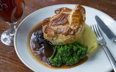 A close up photograph of a Sunday lunch made with a puff pastry pie, mash, red cabbage and Tenderstem broccoli