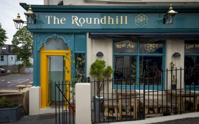 Exterior of The Roundhill with teal and mustard paintwork and outside tables.