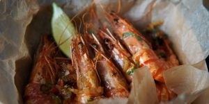 King prawns in rum caramel with a wedge of lime, served in paper