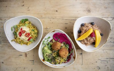 Triangular bowls of food including a bowl of porridge with fresh fruit, a bowl of salad with falafel and beetroot houmous.
