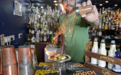 A Bartender in a green t-shirt sets fire to limes with sprinkles of sugar