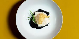 Brill with squid ink velouté , oyster tempura and samphire. Photographed on a mustard yellow table.