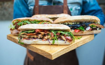 Giant baguettes displayed on a wooden board filled with finest quality meats and veggies mixing together marinades and sauces.