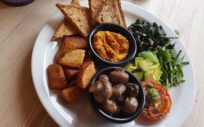 A vegan full english breakfast, avocado, wilted greens, grilled tomato, mushrooms, potato wedges and toast.