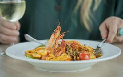 Seafood pasta served in a large white dish and a person holding a glass of white wine in the background.