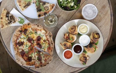 Overhead view of pizza, dough balls and sides on a round wooden table.
