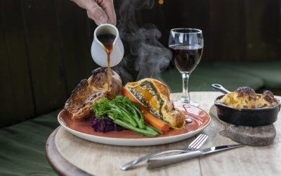 Gravy being poured over a Sunday roast, with roast wellington, Yorkshire pudding carrots, broccoli and cabbage. Red wine and a side of cauliflower cheese are in shot.