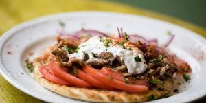 A plate of flatbread, slice tomatoes and meat at Adelfia Greek Restaurant Brighton
