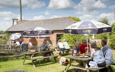 Countryside beer garden with people sitting at tables with parasols