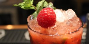 A raspberry cocktail with crushed ice and a spring of mint.